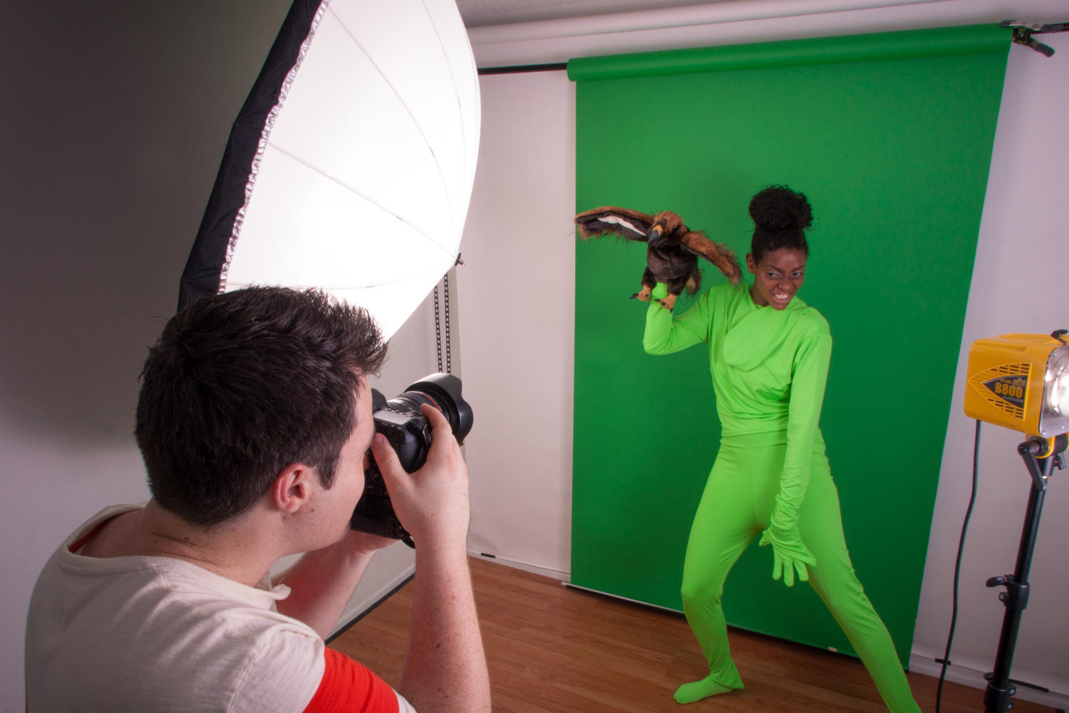 girl on green screen holding puppet