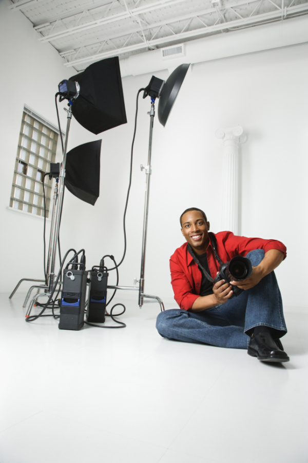 male photographer sitting on ground of studio