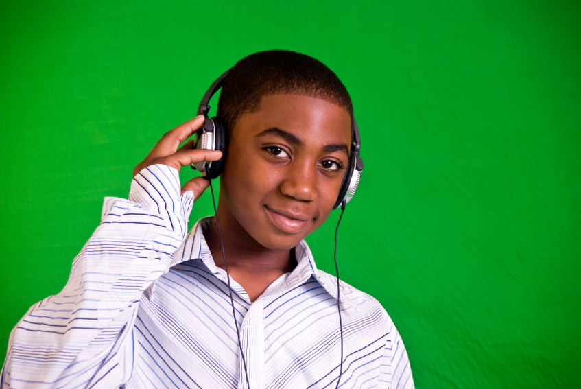 young boy with headphones on on green screen