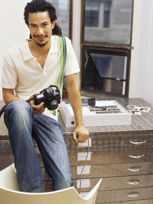 male photographer holding camera sitting on desk