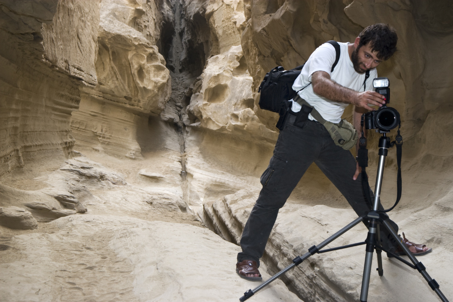 male photographer setting up camera in canyon