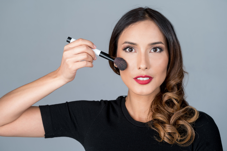 Portrait of a beautiful Asian or Latin American woman applying makeup in front of savage stone gray seamless paper